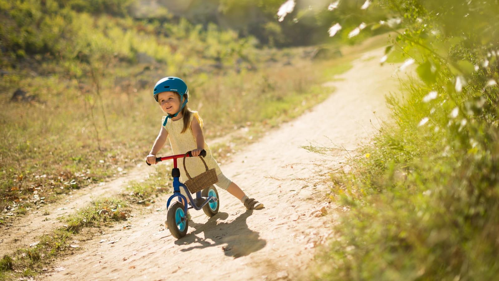 Petite fille à vélo sur un sentier de prairie