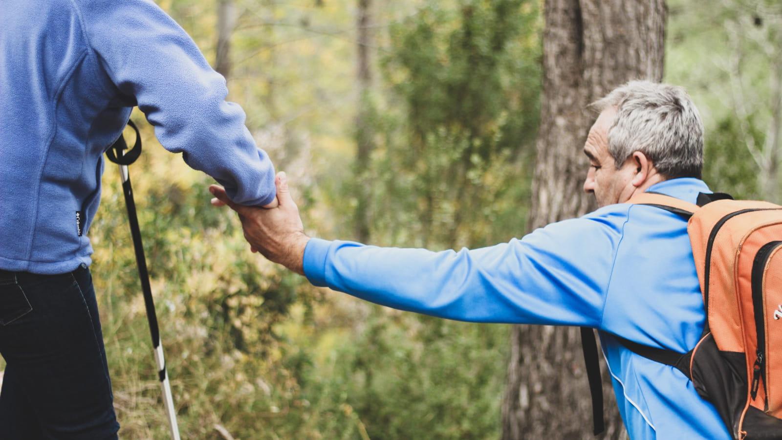 Homme en train d'en aider un autre lors d'une randonnée en forêt